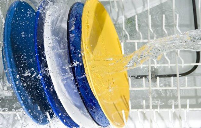 Тарелки в процессе мойки в посудомоечной машине