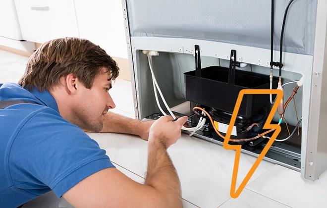 Мастер осматривает холодильник бьющийся током