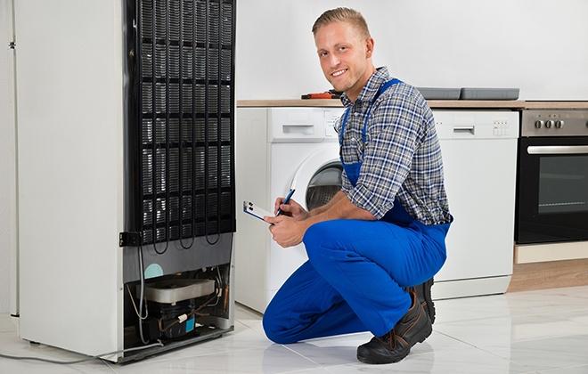 Мастер ремонтирует холодильник
