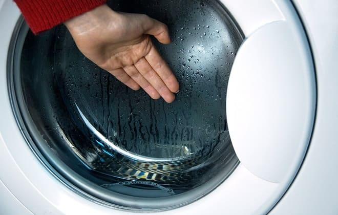 Руку прикладывают к стеклу загрузочного люка стиралки