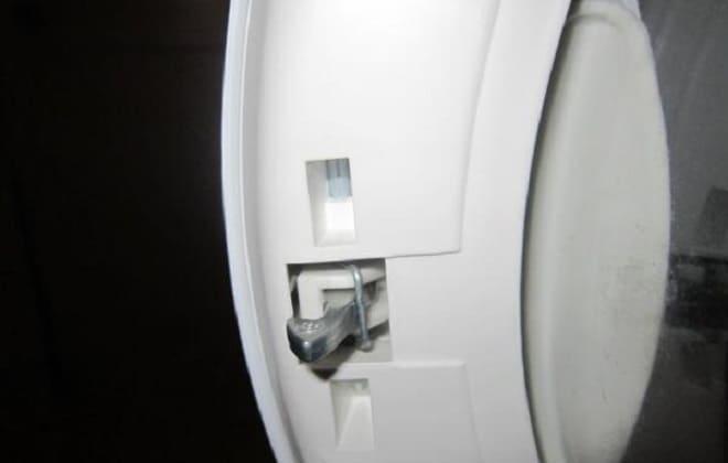 В дверце стиральной машины LG крючок