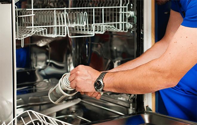 Мастер занимается ремонтом посудомойки