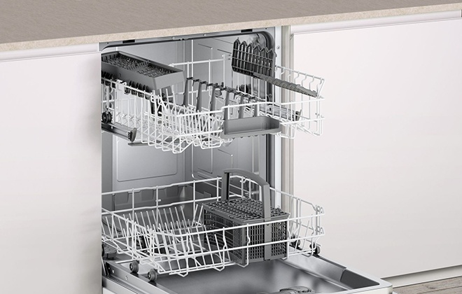 Открытая дверца во встроенной посудомойке