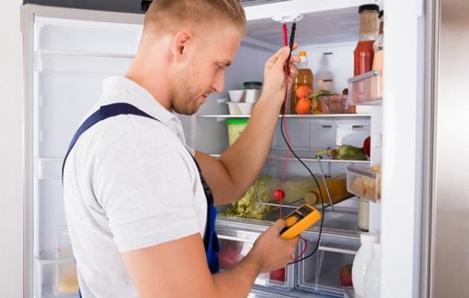 Мастер измеряет напряжение в холодильнике