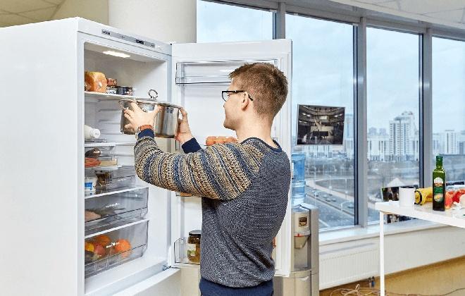 Мужчина ставит кастрюлю в холодильник