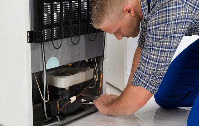 Мужчина в работе над холодильником